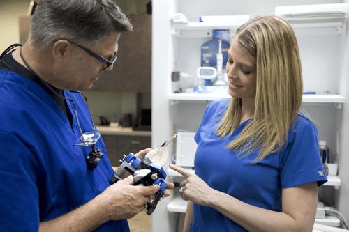 Steven Maurstad and dental assistant, inspecting model. Omaha Dentist, Restorative dentisty
