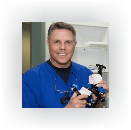 Steven Maurstad DDS holding dental device, Omaha Dentist, Denture, dental implants, crowns and bridges