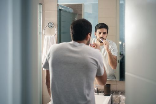 Man looking in mirror brushing his teeth. | Maurstaf family denstistry.
